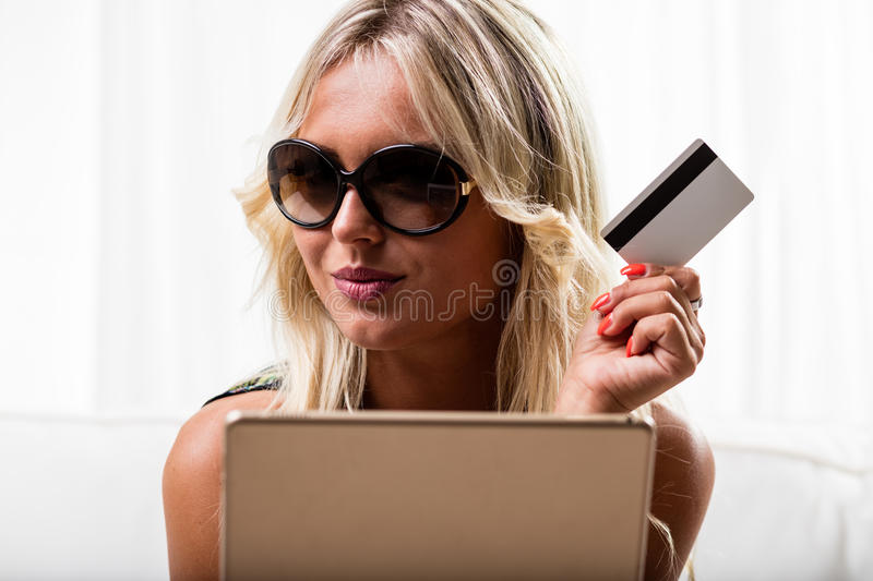 Grinning woman with credit card and tablet royalty free stock image