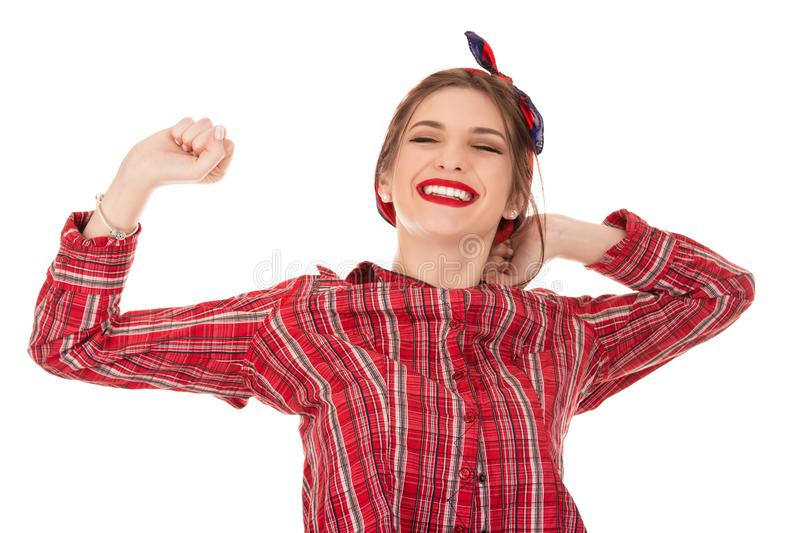 Grinning young woman stretching. Grinning young woman in red long sleeve checkered shirt stretching isolated on white background. Closeup cutout portrait of a stock photography