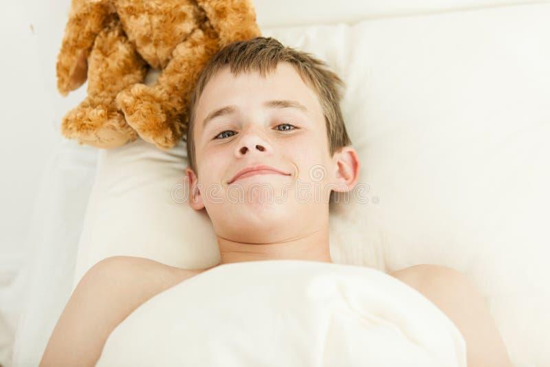Grinsender Junge im Bett bedeckt mit Decke lizenzfreie stockfotografie