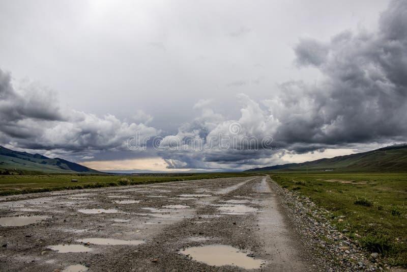 Grintweg die door een bergvallei onder een stormachtige hemel overgaat royalty-vrije stock foto
