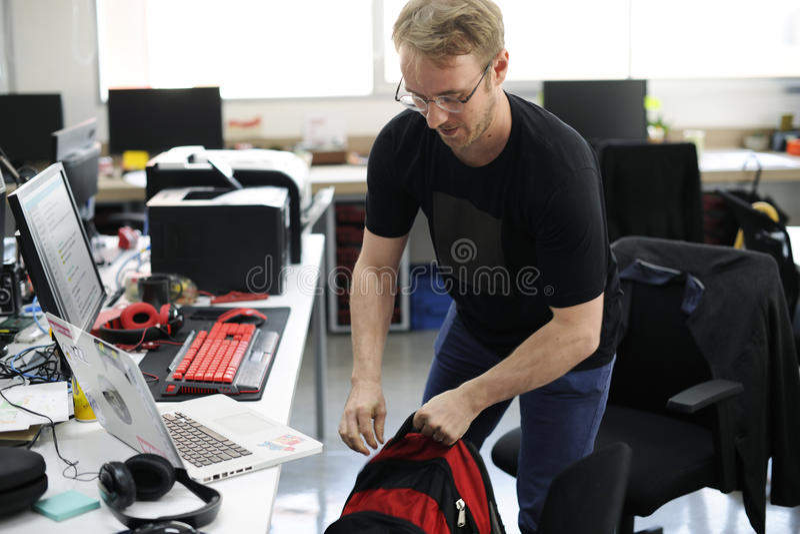 Gripande ryggsäck för man som lämnar efter arbetstimme royaltyfria bilder