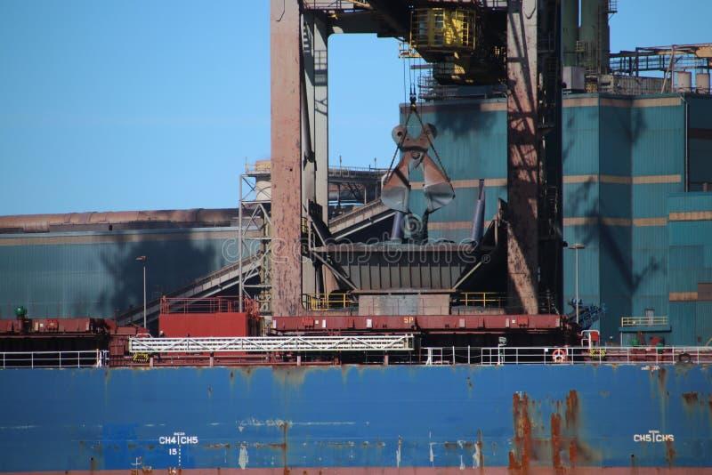 Griparen lastar av havsskeppet med kol in i hopperen för steelwor arkivfoton