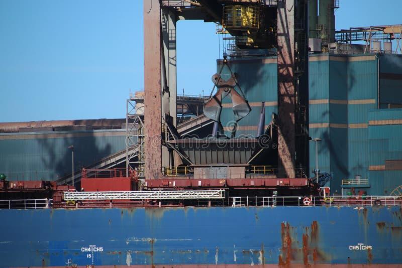 Griparen lastar av havsskeppet med kol in i hopperen för steelwor fotografering för bildbyråer