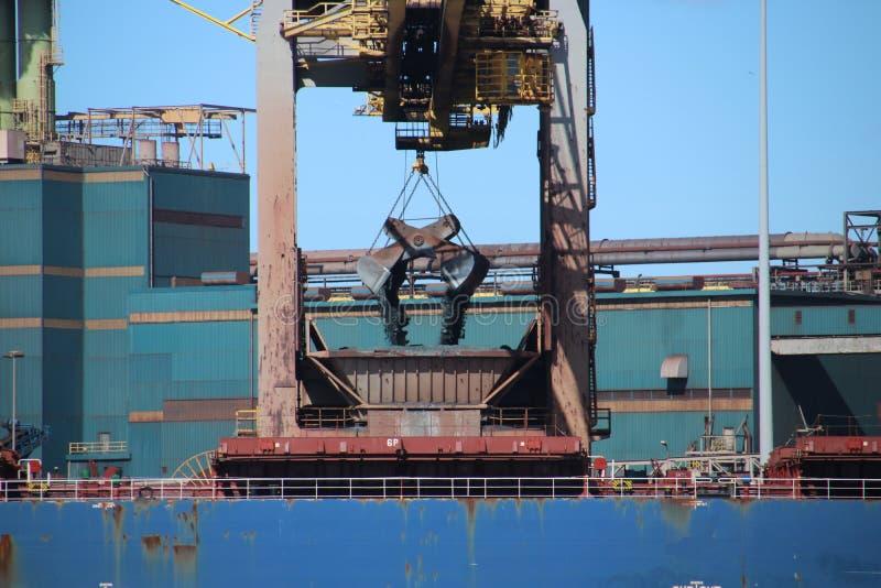Griparen lastar av havsskeppet med kol in i hopperen för steelwor arkivfoto