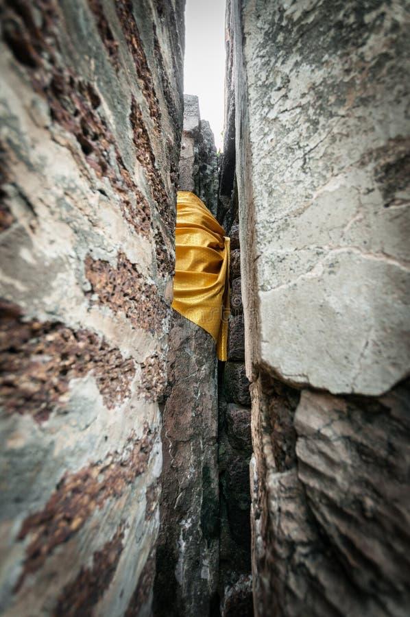 Grippage jaune de tissu de plan rapproché du mur en pierre, bouddhisme traditionnel s images libres de droits