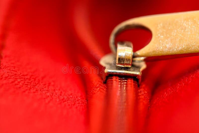 Grippaggio parzialmente aperto della chiusura lampo insieme due strati del tessuto rosso del tessuto e del cuoio rosso nell'ambit immagine stock