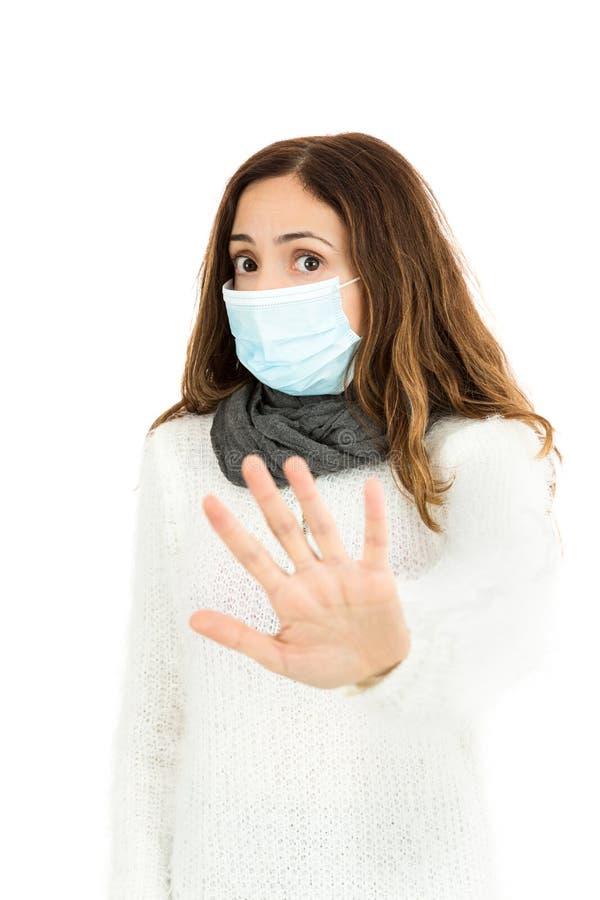 Grippefrau mit einer Virusmaske, die Stoppschild gibt lizenzfreies stockbild