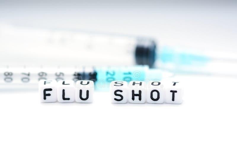 Grippeimpfungstext buchstabierte mit den mit Ziegeln gedeckten Buchstaben, die nahe bei einer Spritze stehen lizenzfreie stockfotografie