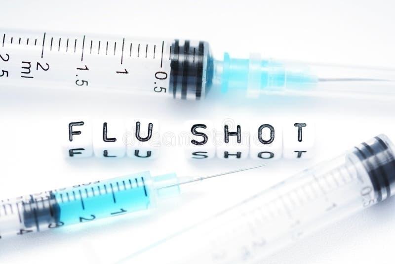 Grippeimpfungstext buchstabierte mit den mit Ziegeln gedeckten Buchstaben, die nahe bei einer Spritze stehen lizenzfreies stockbild