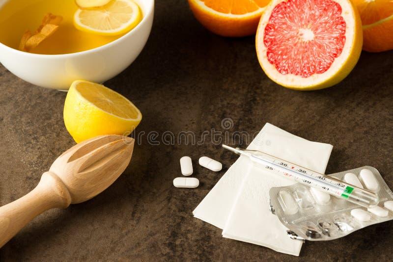 Grippemörder - Vitamine von der Zitrusfrucht, vom Tee mit Ingwer, von den Pillen, vom Thermometer und von den Geweben stockfotos