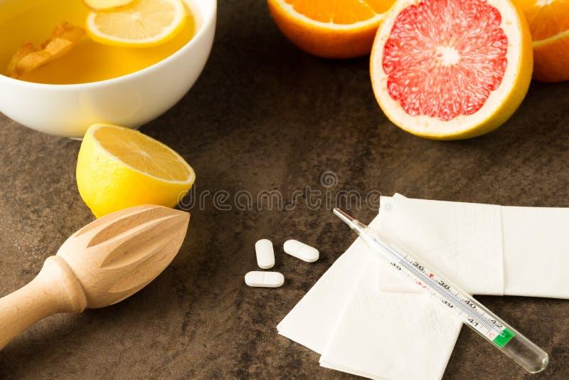 Grippemörder - Vitamine von der Zitrusfrucht, vom Tee mit Ingwer, von den Pillen, vom Thermometer und von den Geweben lizenzfreies stockbild