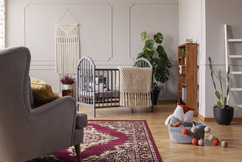 Gris e interior elegante del sitio del bebé con el pesebre de madera y agremán hecho a mano en la pared vacía foto de archivo