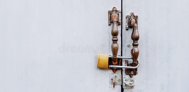 Gris ou porte ou fenêtre grise avec la poignée brune de cru et verrouillée avec la clé machine d'or image libre de droits