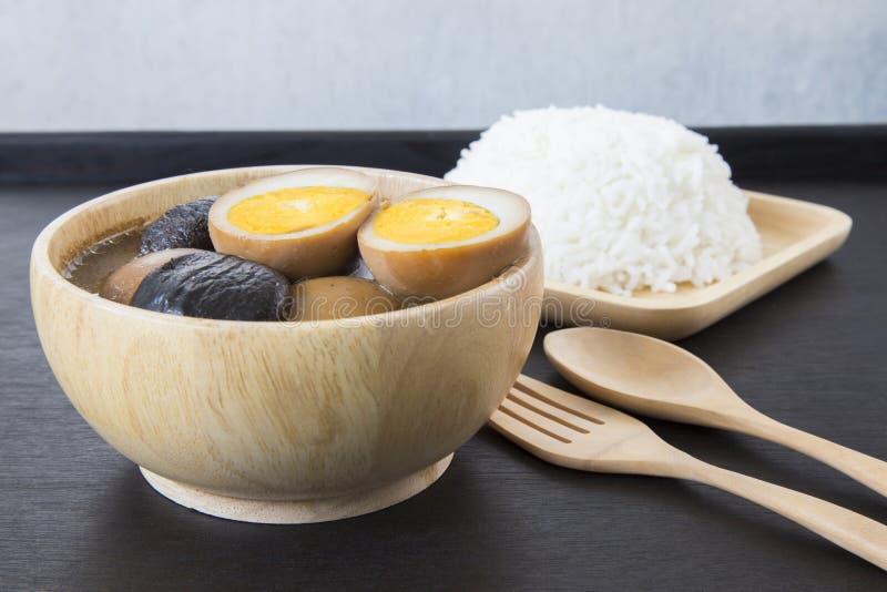Griskött och ägget för fem krydda låter småkoka med träkitchenware på svarta lodisar arkivbild