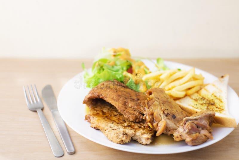 Griskött- och hönabiff med sallad och stekt fransman royaltyfri foto