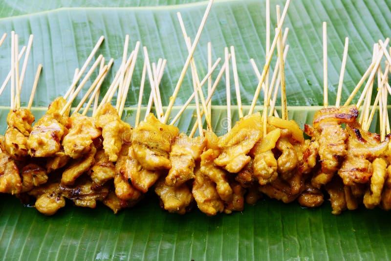 Griskött Satay med din jordnötsås på bananbladet arkivfoto