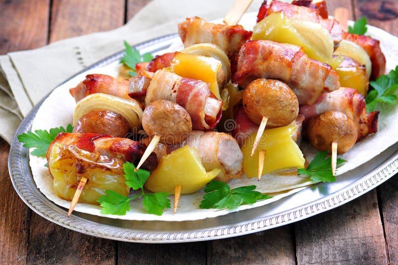 Griskött som slås in i bacon på steknålar som grillas med lökar, champinjoner och peppar arkivfoto