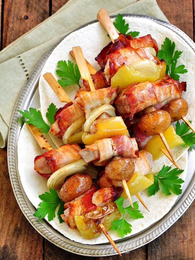 Griskött som slås in i bacon på steknålar som grillas med lökar, champinjoner och peppar royaltyfri fotografi