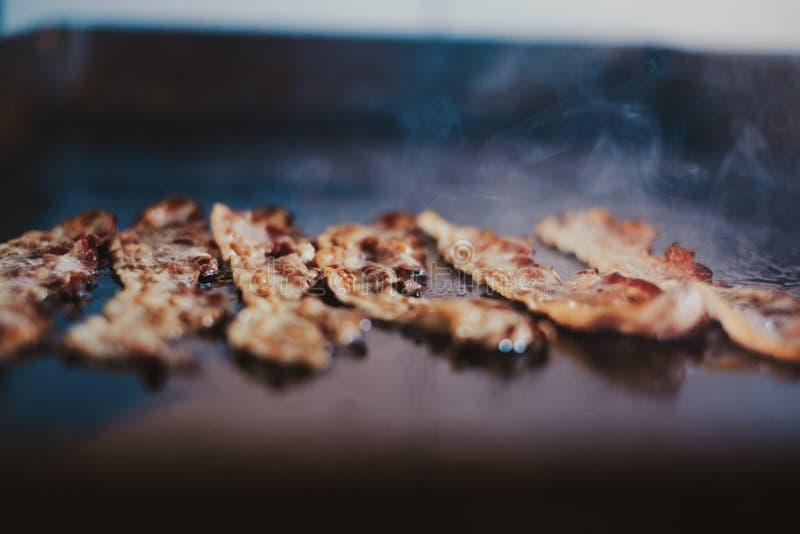 Grisköttbacon som steker på kökgallret royaltyfri bild