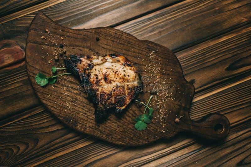 Grisköttbenbiff på brädeen träbakgrund med kenzy honung, peppar arkivfoto