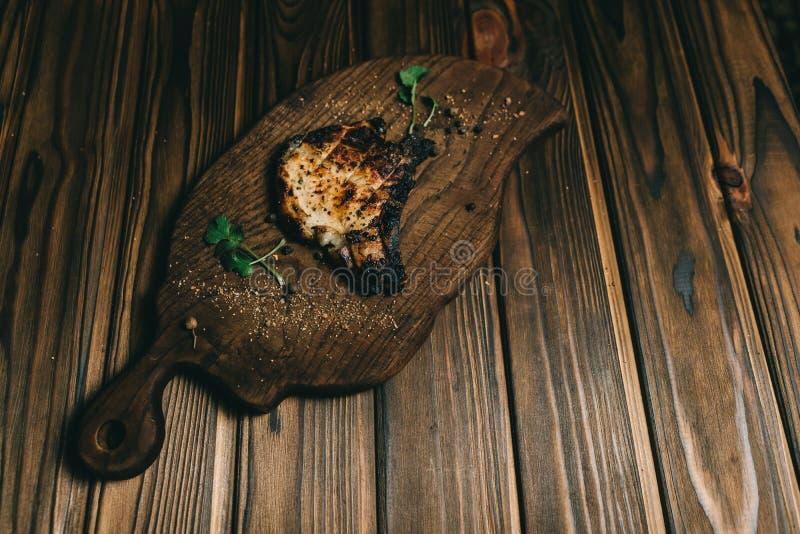 Grisköttbenbiff på en woPorkbenbiff på brädeen träbakgrund med honoden bakgrund med honung Br?det kritiserar kenza peppar arkivbild