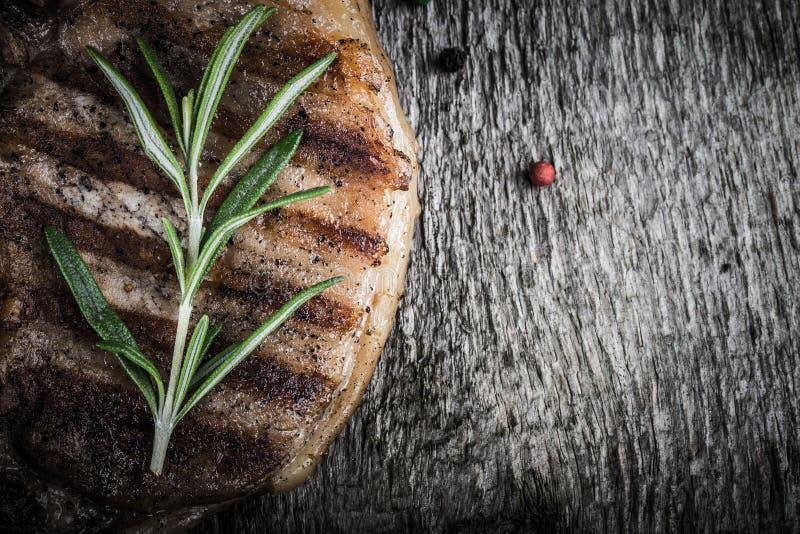 Grisköttbiff med rosmarin och peppar på den gamla trätabellen tonat royaltyfria foton