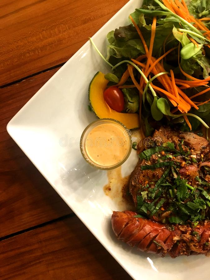 Grisköttbiff och korv med kryddig växt- sås och sallad med dressingen i plattapu arkivfoto