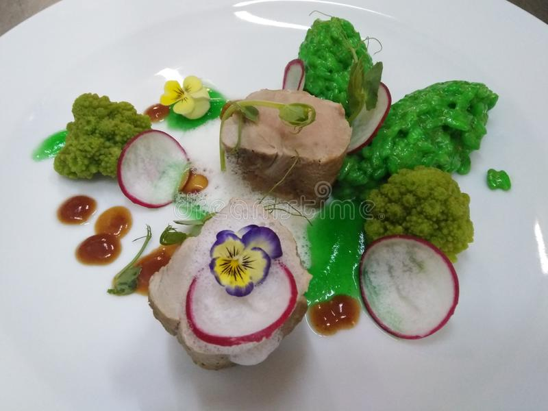 Grisköttfläskkarré med grön rissoto royaltyfria bilder