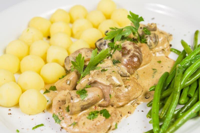 Grisköttfläskkarré med potatisar och lös champinjonsås och haricot vert på den vita plattan royaltyfri foto