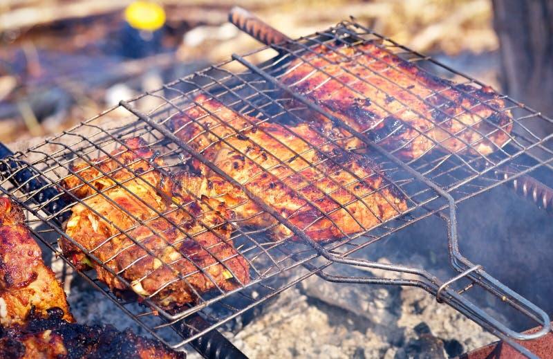 Grisköttkött som grillas på gallret arkivbilder