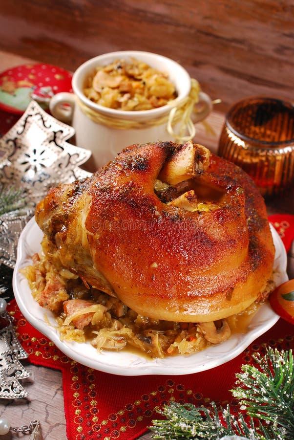 Grisköttknoge med surkålen för julmatställe arkivfoto