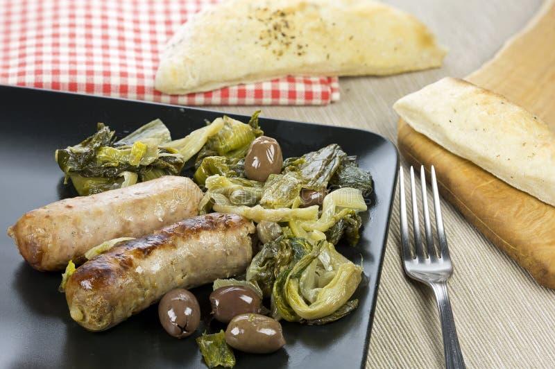 Grisköttkorvar med oliv, royaltyfri foto