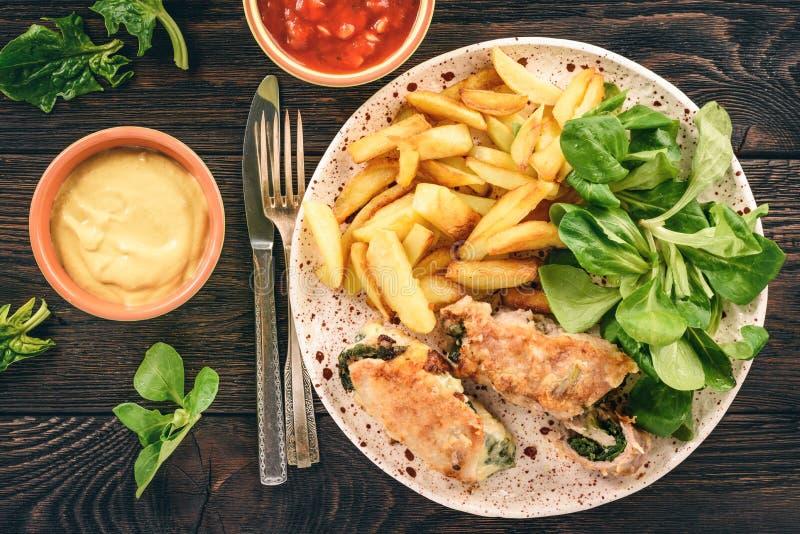 Grisköttroulades med spenat- och ostfyllning som tjänas som med stekte potatisar royaltyfri fotografi