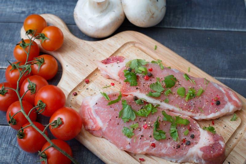 Grisköttskivor med kryddor och örter med en filial av den körsbärsröda tomaten royaltyfria bilder