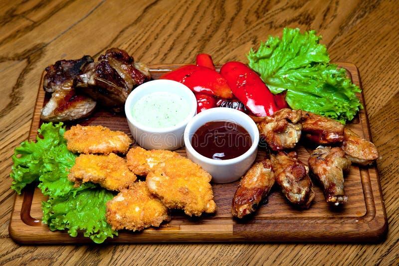 Grisköttstöd med honungsås, kryddiga fega vingar, grillade peppar, fega klumpar, grillfestsås, vitlöksås royaltyfria foton