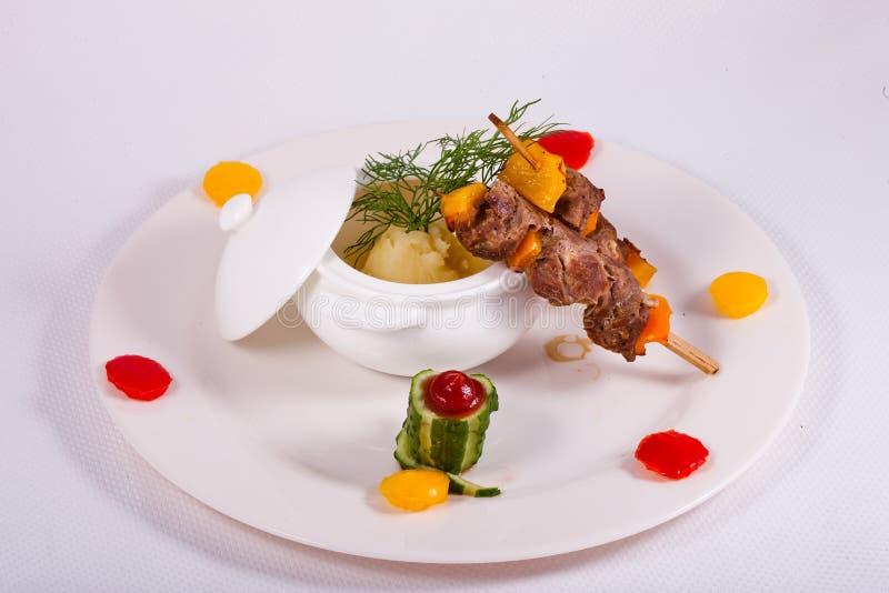 Grisköttsteknålen tjänade som med den mosade potatisen och dekorerade gurkan arkivfoton