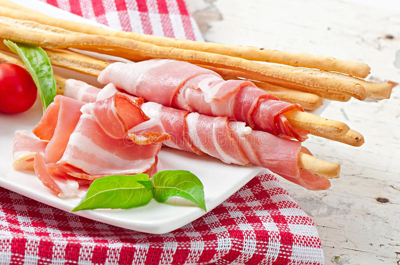 Grissini bread sticks with ham, tomato and basil stock photos
