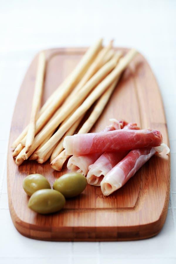 Grissini con el jamón y las aceitunas foto de archivo libre de regalías