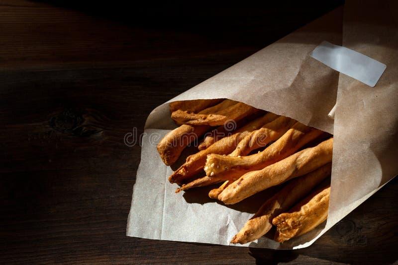 Grissini de batons de pain avec les graines de sésame dans le paquet de métier sur un fond en bois images stock