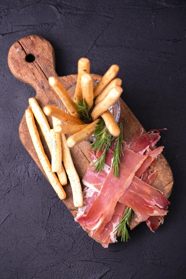 Grissini tradicional de las barras de pan italiano con el jamón de prosciutto foto de archivo libre de regalías