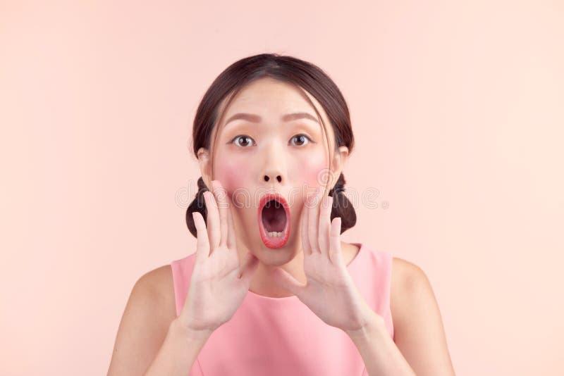 Gritaria asiática nova surpreendida da mulher sobre o fundo cor-de-rosa imagens de stock