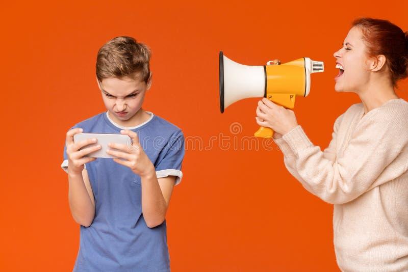 Gritaria da m?e atrav?s do megafone no menino com manche foto de stock
