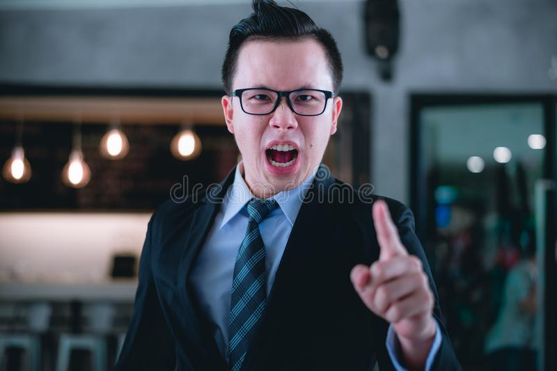Gritaria do gerente e dedo apontar no empregado porque está muito irritado dos relatórios de vendas e dos relatórios financeiros  imagem de stock royalty free