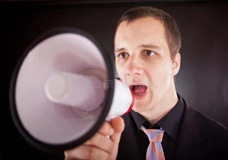 Gritaria do homem de negócios através do megafone imagens de stock royalty free