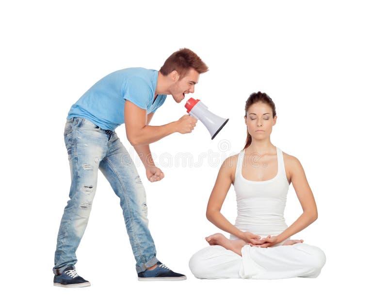 Gritaria do homem novo através de um megafone em uma mulher ao fazer o yo fotografia de stock