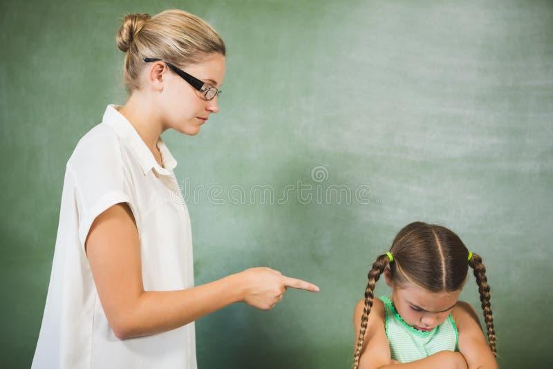 Gritaria do professor fêmea na menina na sala de aula fotos de stock