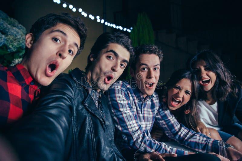 Gritaria dos amigos e selfie engraçados da tomada no partido imagem de stock royalty free