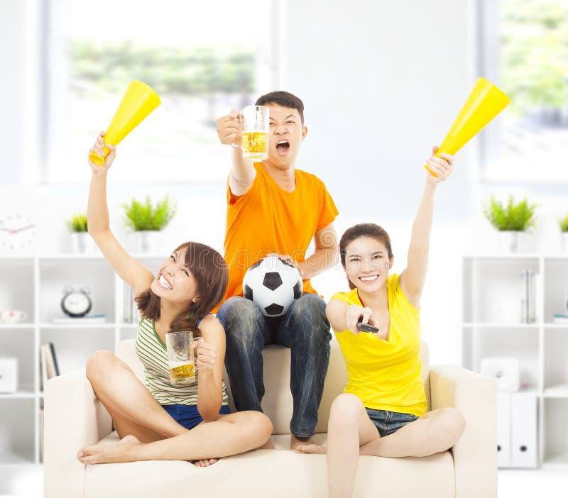 Gritaria dos jovens para incentivar em casa sua vitória da equipe fotografia de stock royalty free
