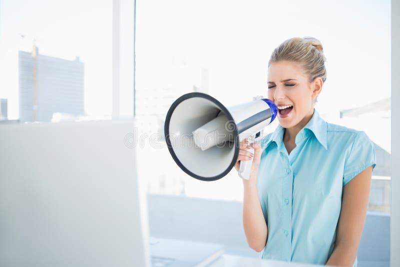 Gritaria furioso da mulher elegante no megafone imagens de stock