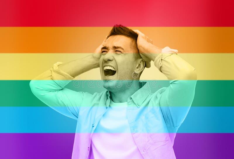 Gritaria infeliz do homem gay sobre a bandeira do arco-íris fotos de stock